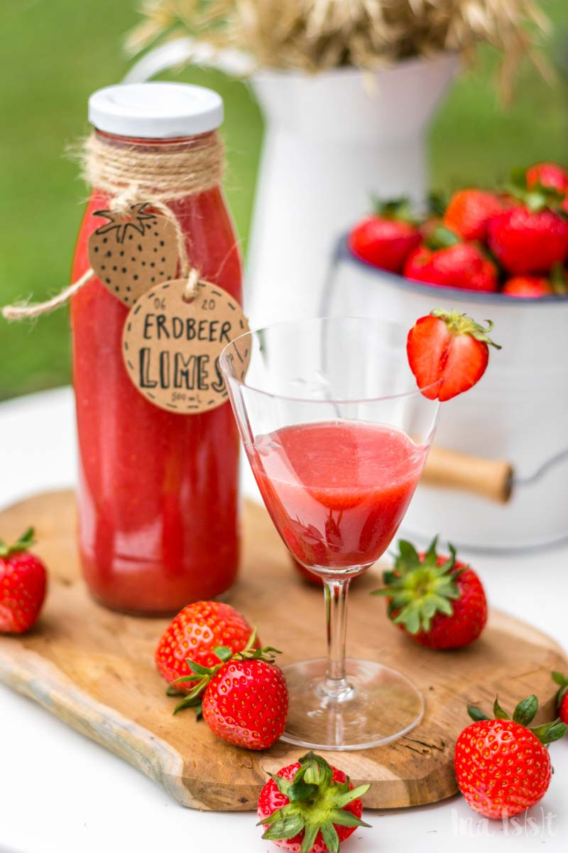 Erdbeer Limes Rezept in Flaschen auf Gartentisch im Grünen, Erdbeer Limes selbermachen, #erdbeerlimes