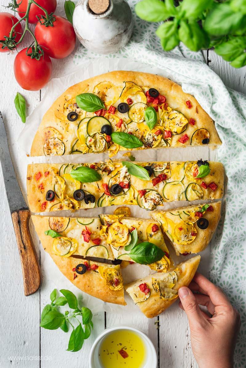 Focaccia Pugliese mit Zucchini und Tomate auf weißem Holztisch